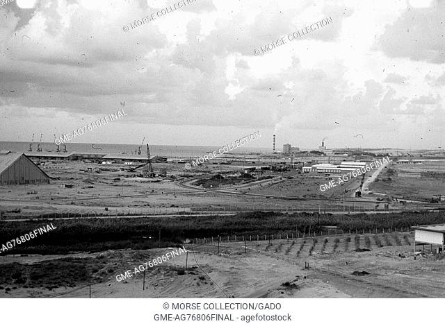 View of buildings, smokestacks, cranes working, and roadways running through El Arish, Gaza, Israel, November, 1967