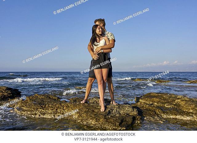 Couple standing on rocks, seaside, holiday, love, lovers. Chersonissos, Crete, Greece