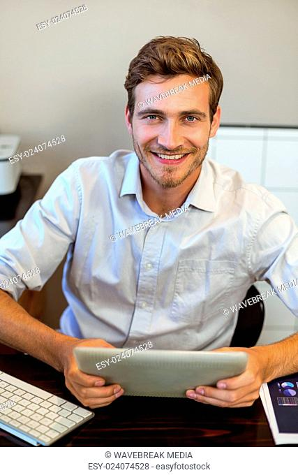 Portrait of smiling man with digital tablet in office