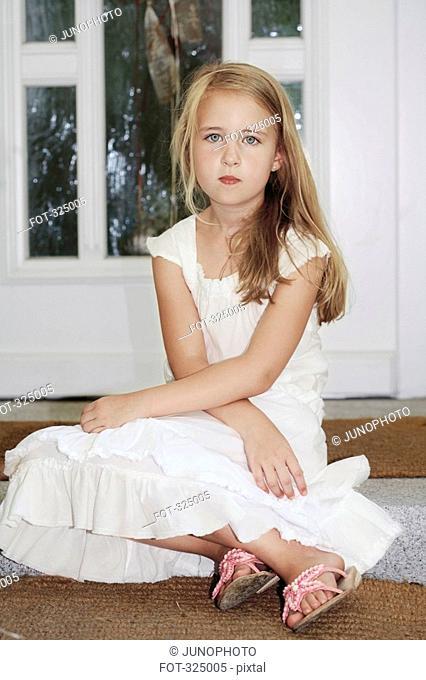Girl sitting on door step wearing white dress
