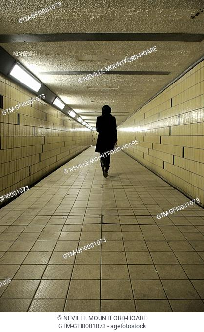 Figure walking away down an underground tunnel