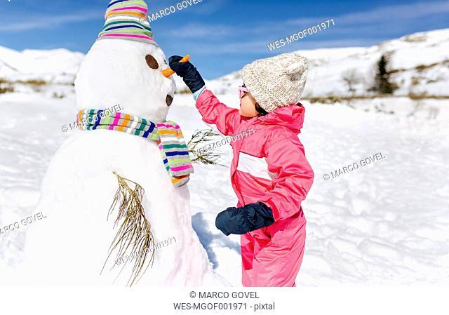 Spain, Asturias, Girl building a snowmen in winter