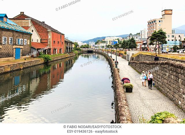 Otaru, historic canal and warehousedistrict in Hokkaido, Japan, with many tourists walking by