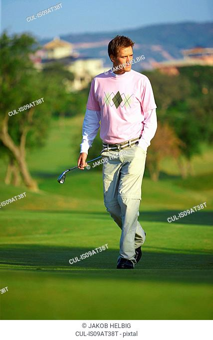 Golfer carrying golf club, hand in pocket looking away