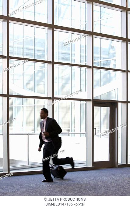 African American businessman running with luggage in lobby