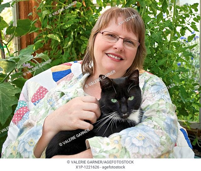 This middle aged woman is smilling and happy as she's holding a black cat with green eyes in a greenhouse She's wearing glasses and in a peaceful theme and...