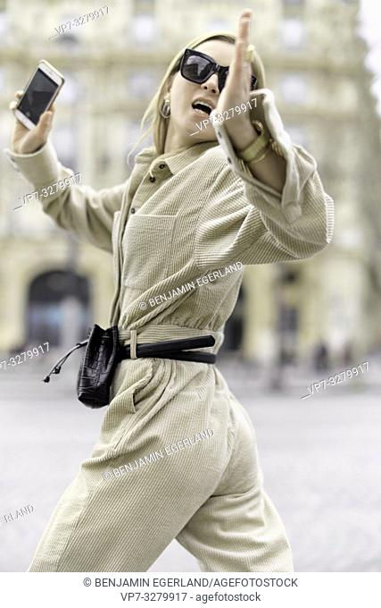 buoyant fashionable woman running at street with smartphone in hand, wearing latest trends, social media fashion blogger during fashion week, in Paris, France