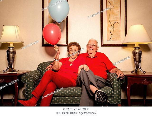 Senior couple on sofa with balloons