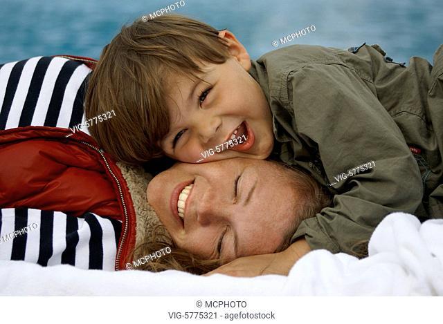 Ein kleiner Junge schmust am Meer mit seiner Mutter , Mittelmeer, Spanien| A little boy is terderly with his mother on the sea - Menorca, Balearen, Spain