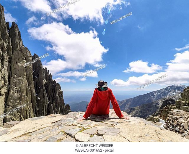 Spain, Sierra de Gredos, hiker sitting on rock in mountainscape