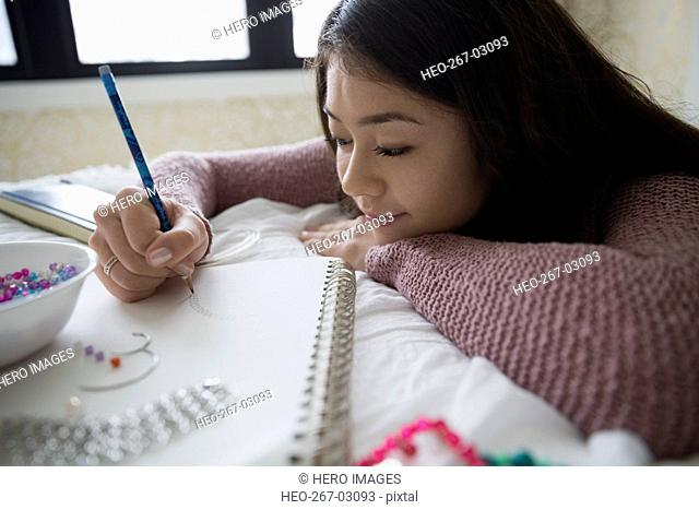 Teenage girl sketching and making jewelry
