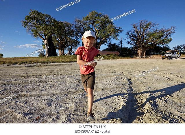 Boy playing on gravel road, Nxai Pan National Park, Kalahari Desert, Africa