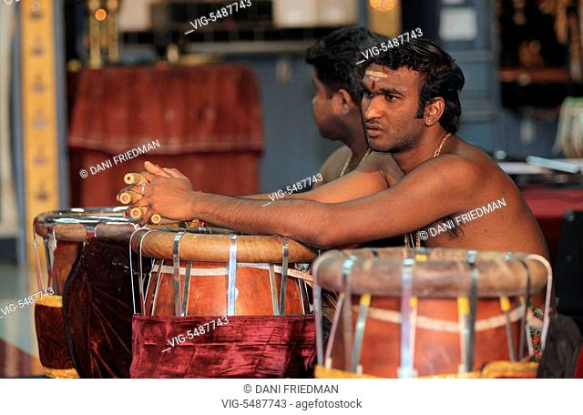 CANADA, BRAMPTON, 08.08.2015, Tamil Hindu musicians take a brief rest from playing a rhythmic tune on the Thavil (a traditional drum) and listen as special...
