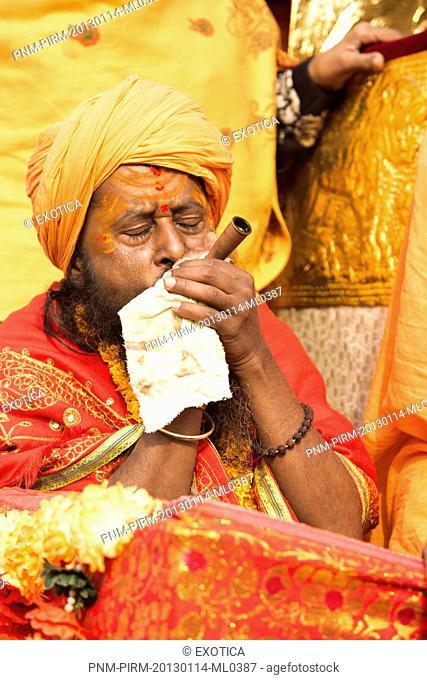 Sadhu smoking a chilam during the first royal bath procession in Kumbh Mela festival, Allahabad, Uttar Pradesh, India