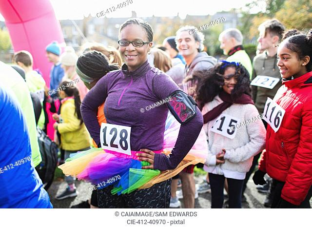 Portrait confident female runner wearing tutu at starting line at charity run