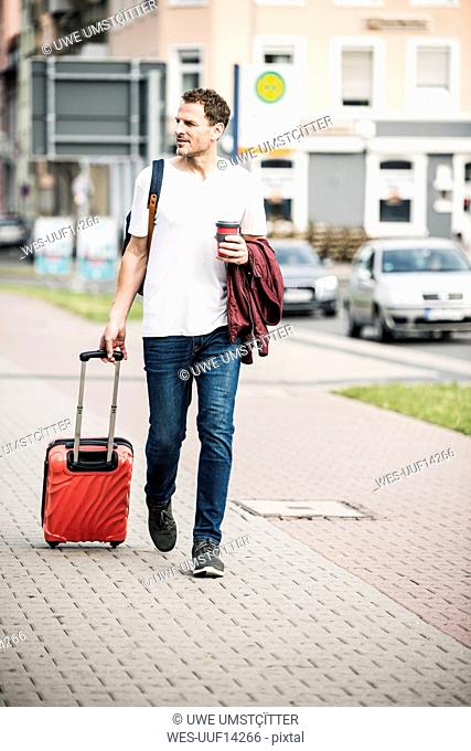 Man with rolling suitcase and takeaway coffee walking in the city