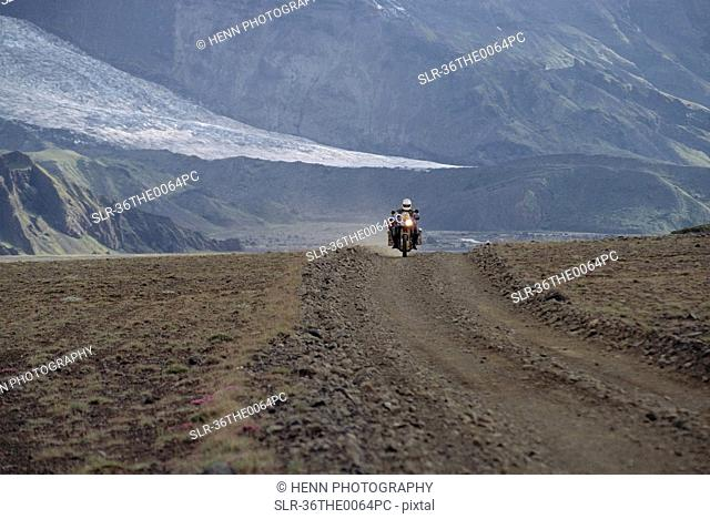 Man driving motorcycle on dirt road