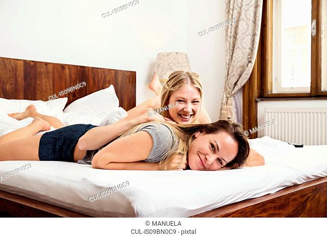 Two women lying on bed, portrait