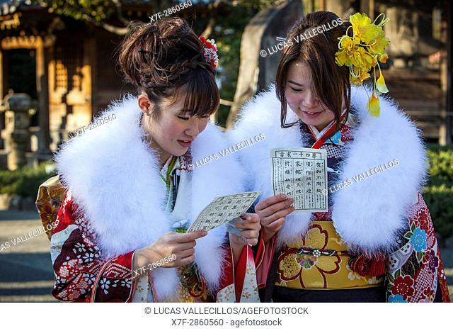 Women in furisode kimono reading their omikuji paper oracle, Seijin no hi day, celebration of the coming of age, second Monday of January