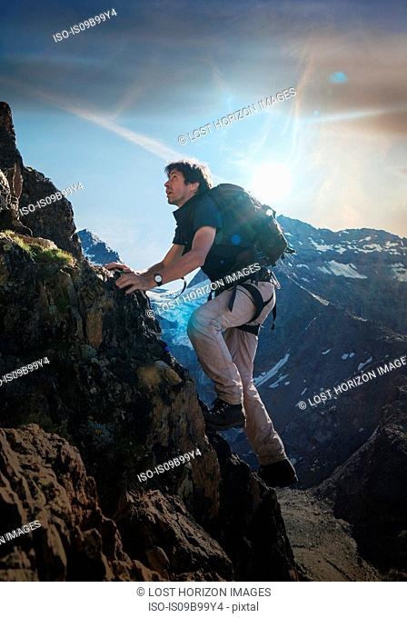 Mature male climber climbing up Jegihorn, Valais, Switzerland