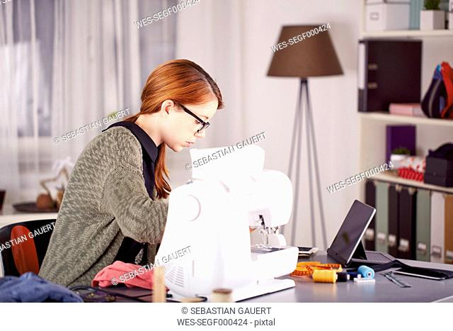 Portrait of young woman using sewing machine at home