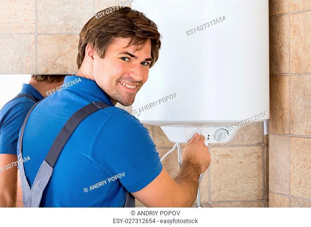 Happy Repairman Holding Knob Of Electric Boiler