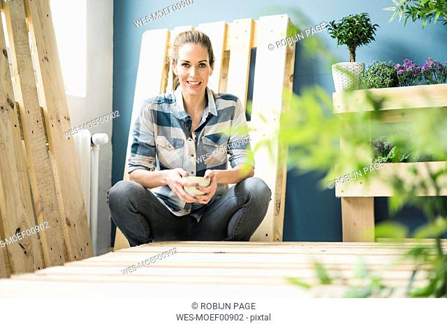Beautiful woman taking a break from refurbishing her home with pallets, drinking coffee