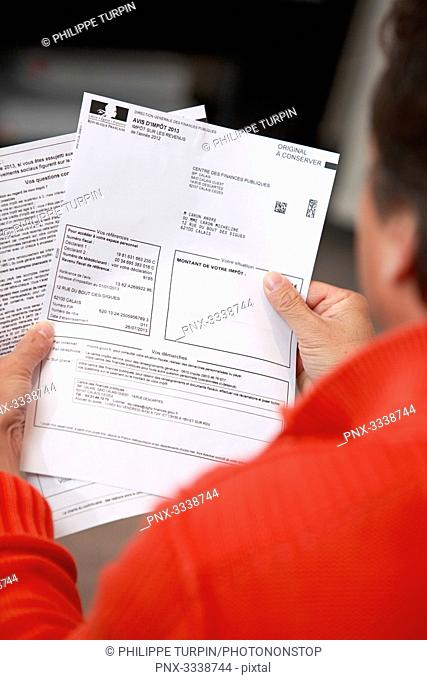 France, Back view of a man holding his tax notice