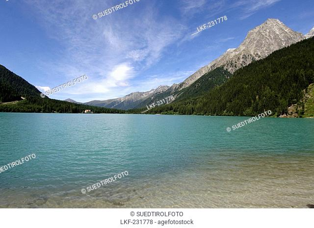 View at Antholzer lake between mountains under blue sky, Val Pusteria, South Tyrol, Italy, Europe