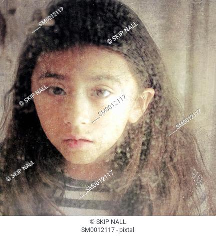 Little girl looking in to a mirror with a sad look on her face