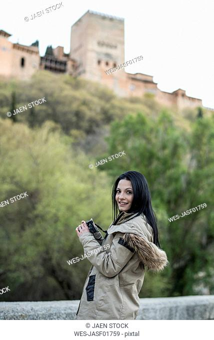 Spain, Granada, smiling young woman taking pictures at the Alhambra
