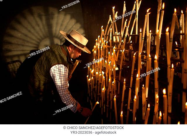 A man, wearing a Spanish hat, lights candles at the Votive Room of the shrine of the Virgin of Rocio, in Almonte, Donana National Park, Huelva province