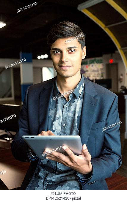 Young millennial businessman using his technology in the workplace; Sherwood Park, Alberta, Canada