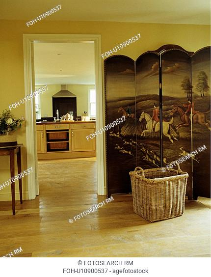 Large basket in front of antique pictorial folding screen beside open doorway with view of neutral kitchen