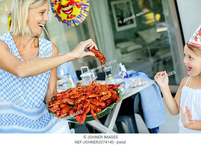 Mature woman and girl with bowl of crayfish