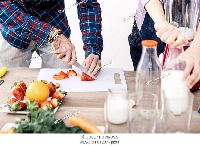 Couple preparing smoothies with fresh fruits and vegetables, partial view