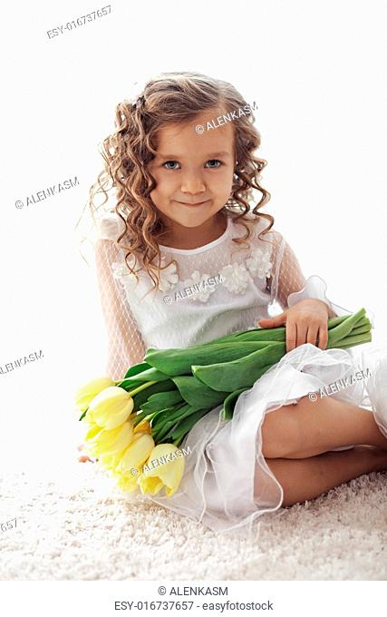 Beautiful little princess wearing flower girl dress posing with the bouquet of spring tulips