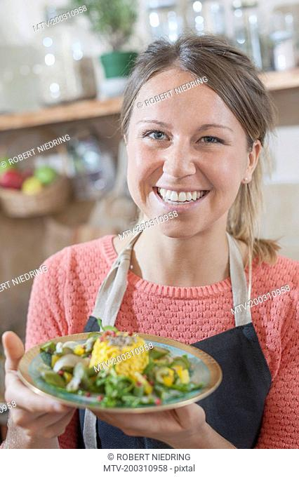 Portrait of woman with garnished rice dish in hand