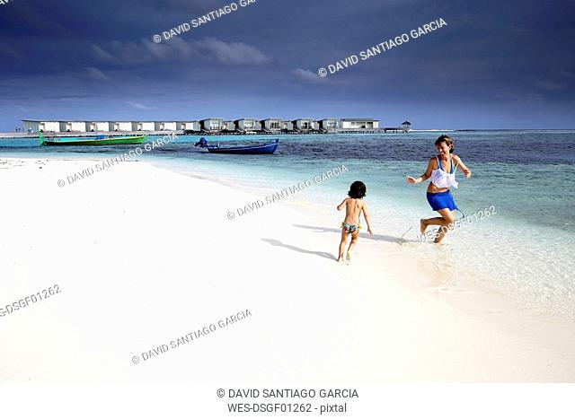 Maldives, Guraidhoo, mother and daugther playing on beach