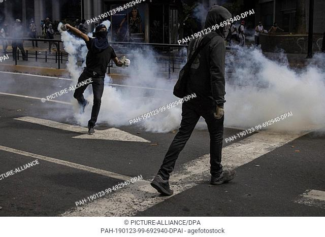 23 January 2019, Venezuela, Caracas: Masked demonstrators throw tear gas at security forces in collisions in Caracas. Thousands of people took to the streets...