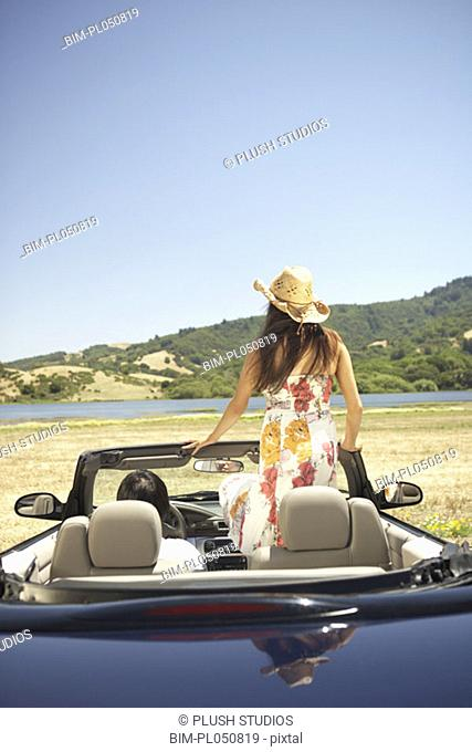 Young woman standing up inside a convertible