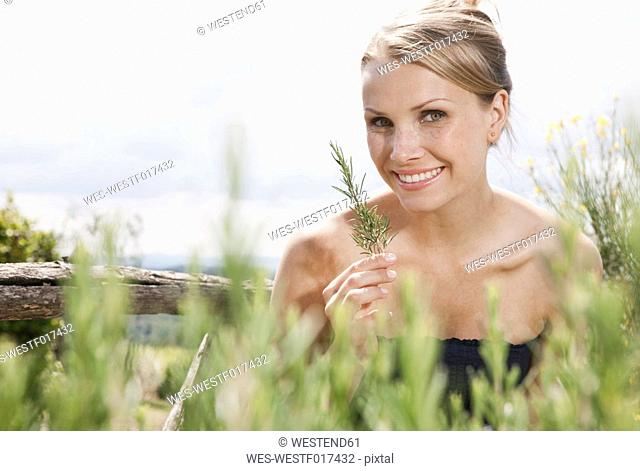 Italy, Tuscany, Magliano, Close up of rosemary plant in front of woman, smiling, portrait