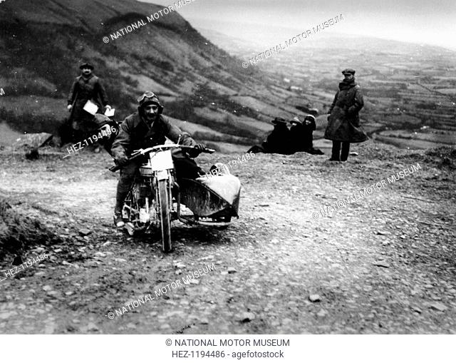 Jack Thomas riding a Norton, competing in the South Wales Trial, 1921. The passenger in the sidecar is leaning completely over the back of the bike's seat