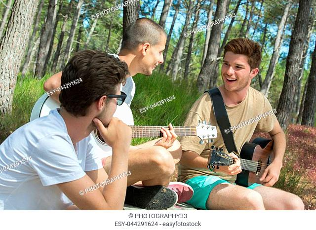 group of smiling tourists playing guitar