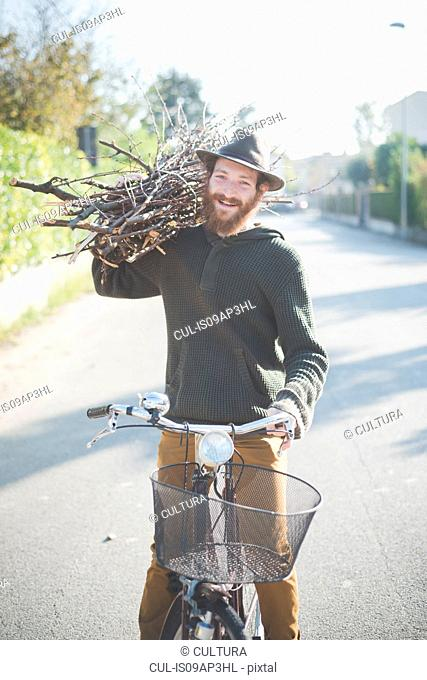 Young man carrying bunch of sticks on shoulder on bike