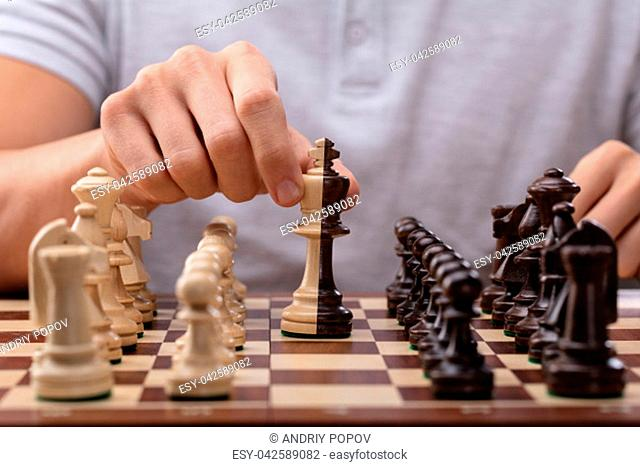 Man's Hand Moving A King Chess Piece