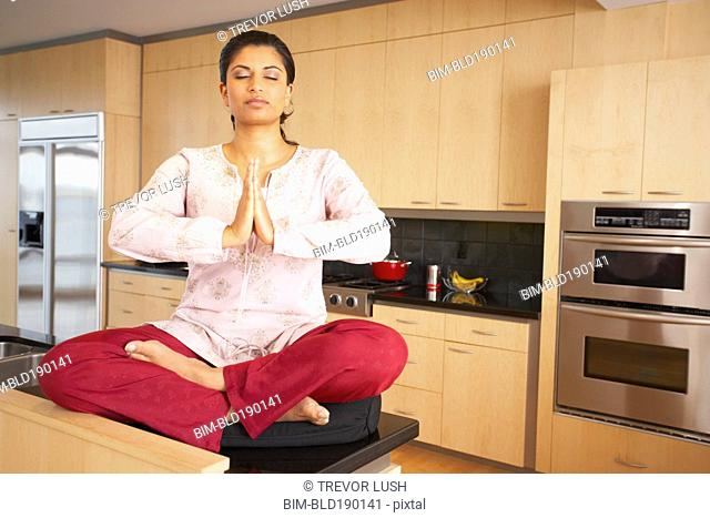 Indian woman meditating in kitchen