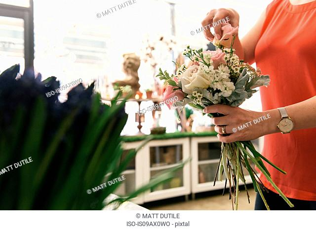 Florist arranging bouquet in flower shop, mid section