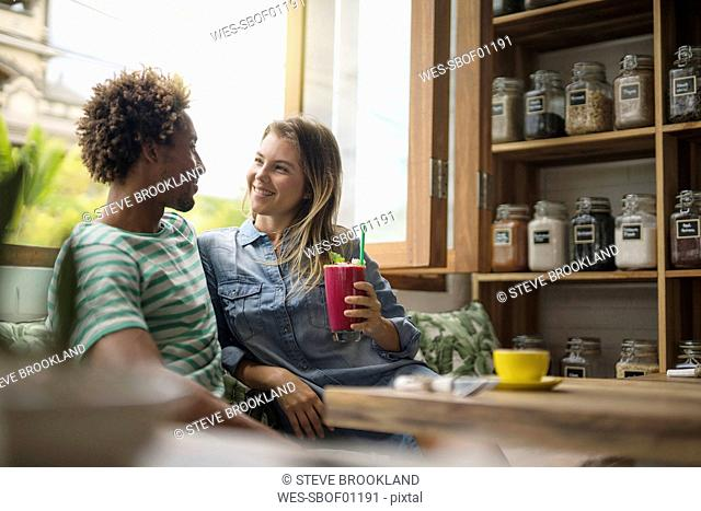 Smiling couple sitting in cozy cafe in front of window