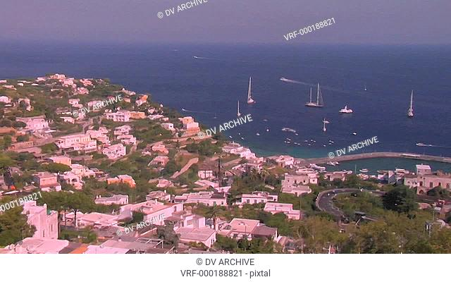 The island of Capri, Italy is visible with ships anchored in the harbor in the distance